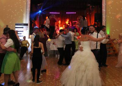 Band für Hochzeit mit Hochzeitsgästen auf Bühne, Tänzer Bräutigam